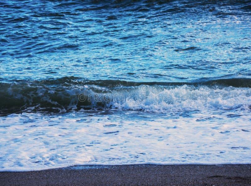 Fermez-vous de l'eau de mer affectant le sable sur la plage, la mer W photos stock