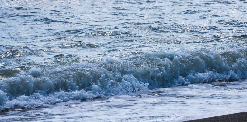 Fermez-vous de l'eau de mer affectant le sable sur la plage, la mer W image stock