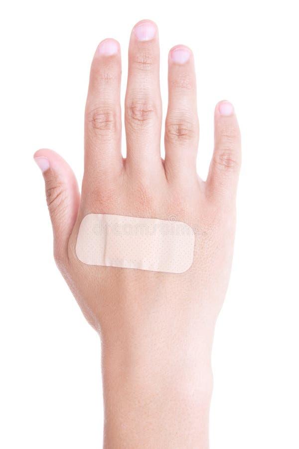 Fermez-vous de l'emplâtre adhésif sur la main masculine d'isolement sur le blanc image libre de droits