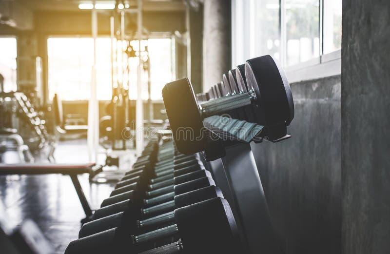 Fermez-vous de l'ensemble d'haltère au gymnase, formation de poids d'équipement sur le support dans le club de sport photos stock