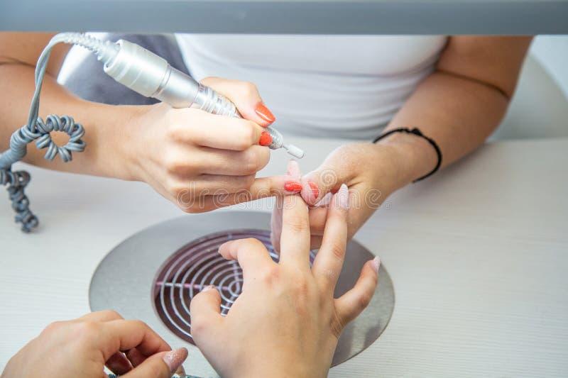 Fermez-vous de l'esthéticien avec l'ongle électrique forent dans le salon de manucure de beauté image stock