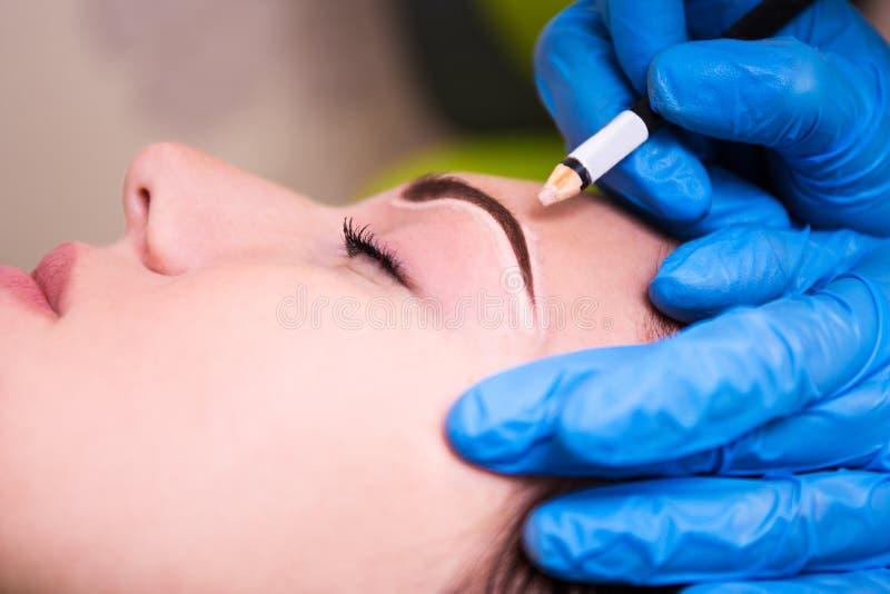 Fermez-vous de l'esthéticien préparant la jeune femme pour l'eyebr permanent images stock