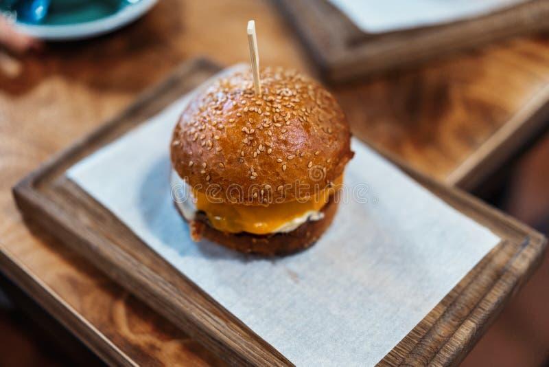 Fermez-vous de l'hamburger juteux frais sur la planche à découper en bois en café photographie stock