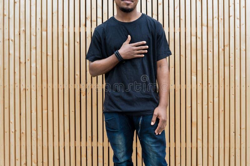 Fermez-vous de l'homme à la peau foncée attirant dans le T-shirt noir sur le fond en bois photographie stock