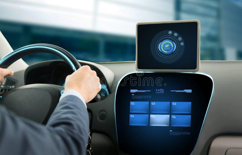Fermez-vous de l'homme avec le PC de comprimé conduisant la voiture image stock