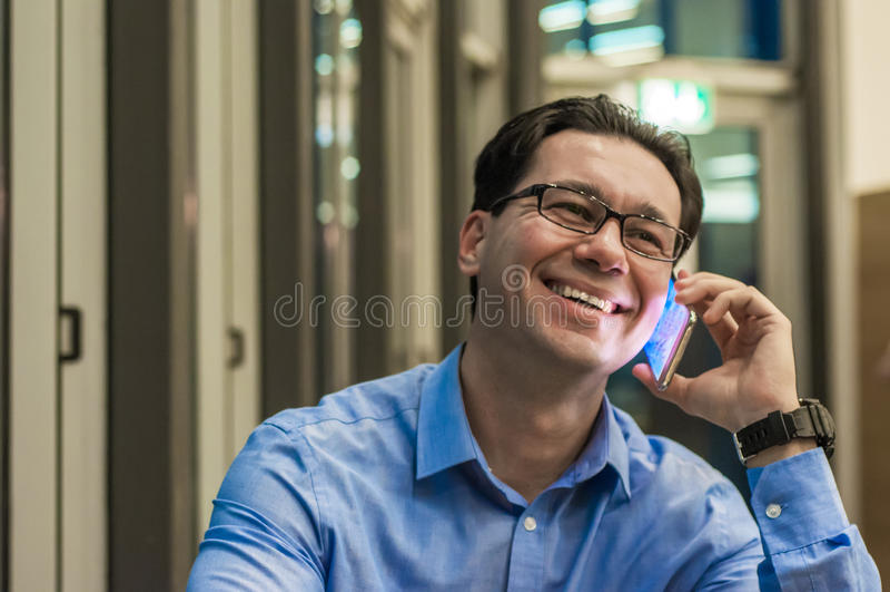 Fermez-vous de l'homme d'affaires de sourire utilisant le téléphone intelligent moderne, photo libre de droits