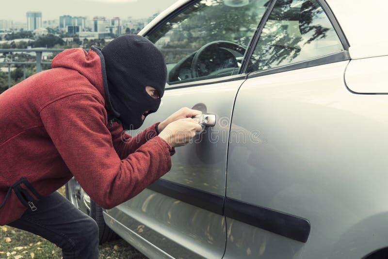 Fermez-vous de l'homme dans le masque noir de voleur cassant la serrure de voiture sur un fond de ville le voleur Malade-prévu fo photo stock