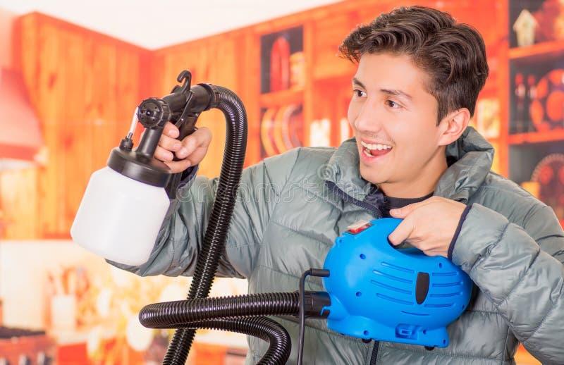 Fermez-vous de l'homme de sourire bel tenant dans des ses mains le pistolet de pulvérisation de peinture, utiliser une veste gris photos stock