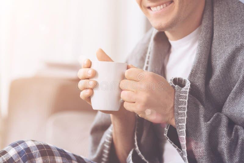 Fermez-vous de l'homme de sourire tout en buvant du thé photos libres de droits