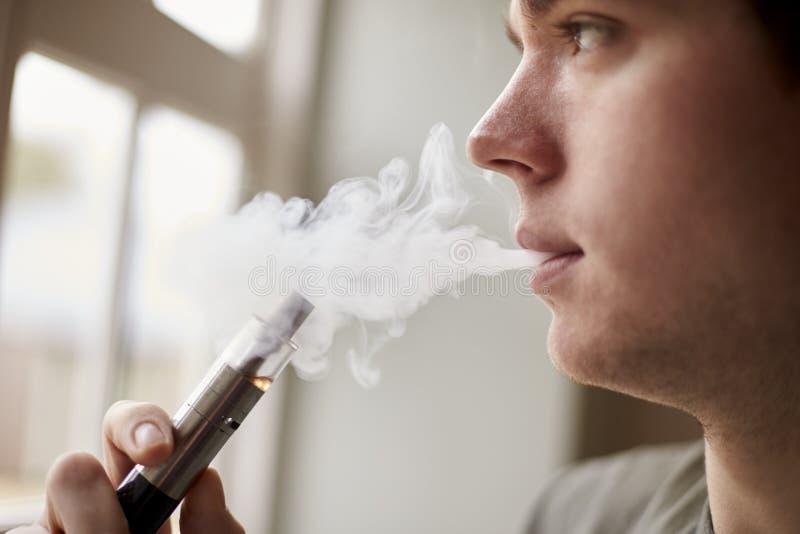 Fermez-vous de l'homme employant Vapourizer en tant qu'alternative de tabagisme photos libres de droits