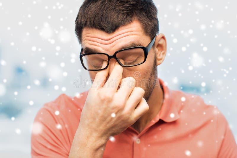 Fermez-vous de l'homme fatigué dans des lunettes frottant des yeux photographie stock libre de droits
