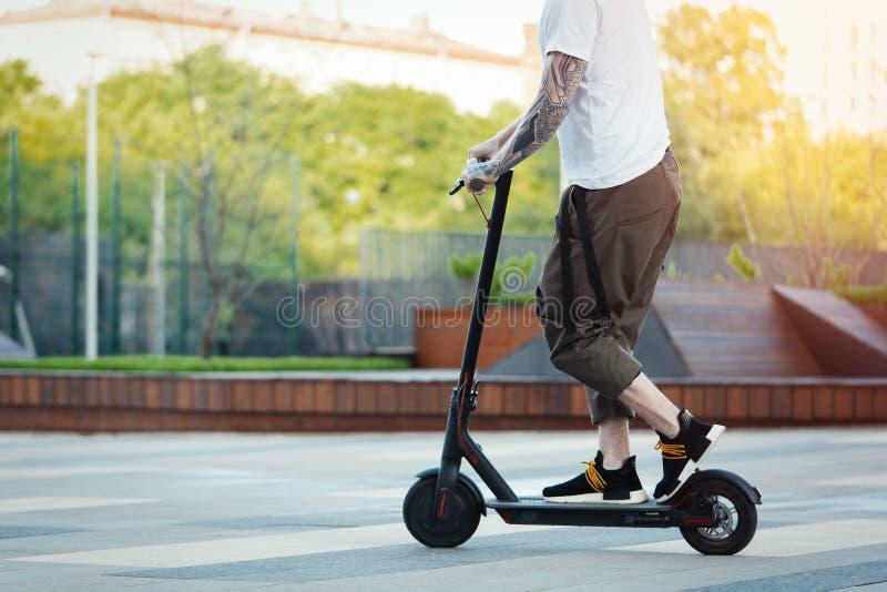 Fermez-vous de l'homme montant le scooter ?lectrique noir de coup-de-pied au beau paysage de parc image libre de droits