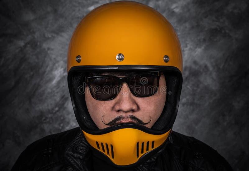 Fermez-vous de l'homme de motard dans le casque de moto et la veste en cuir photos stock