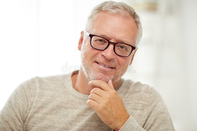 Fermez-vous de l'homme supérieur de sourire dans la pensée en verre image libre de droits