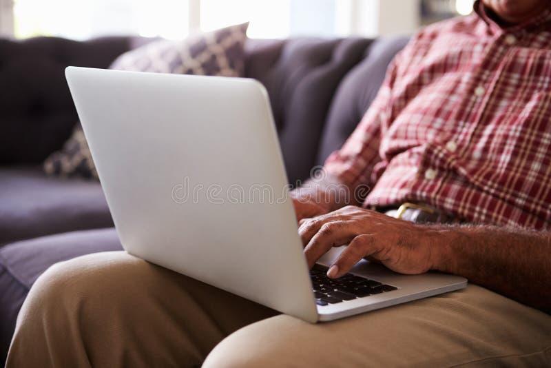 Fermez-vous de l'homme supérieur s'asseyant sur Sofa Using Laptop image stock