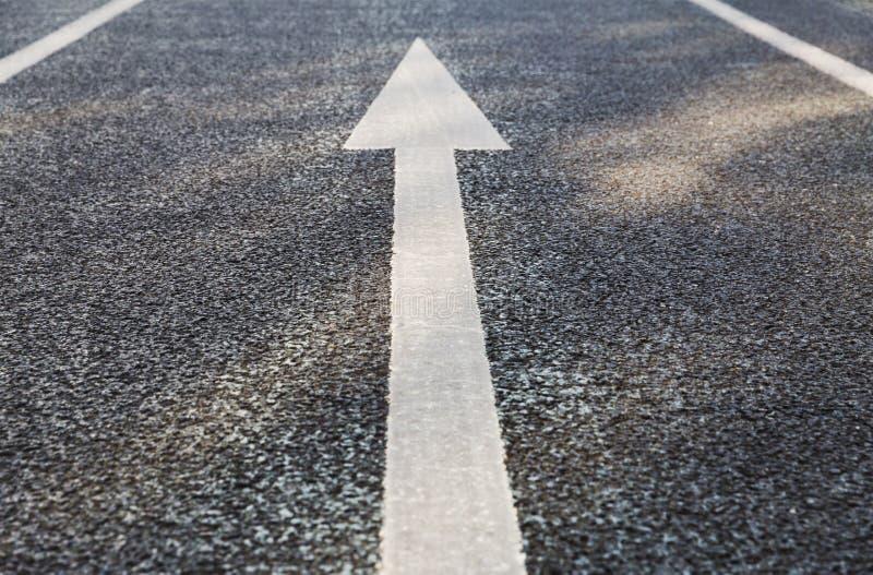 Fermez-vous de l'inscription de couche de surface de flèche sur l'asphalte photos stock