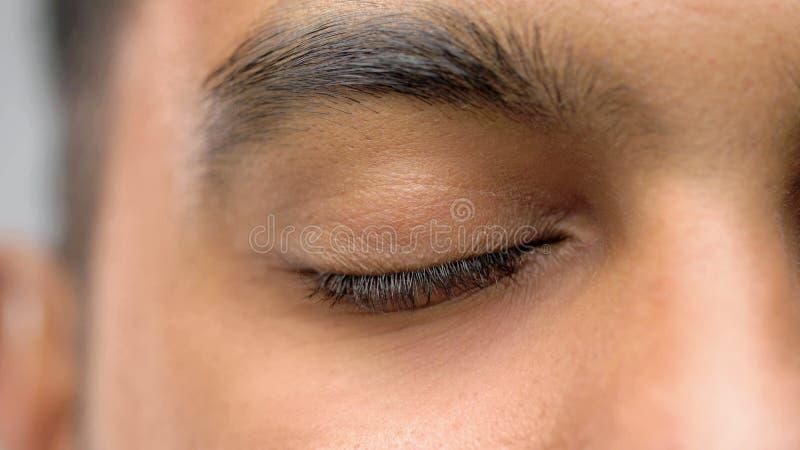 Fermez-vous de l'oeil masculin fermé image stock