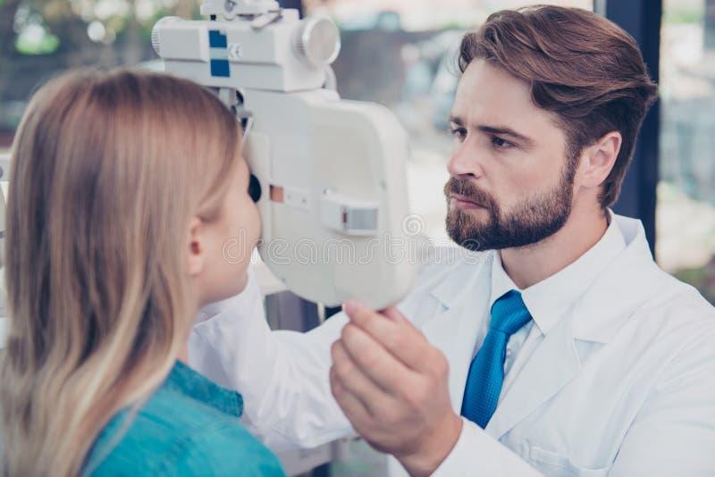 Fermez-vous de l'optométriste barbu châtain de Doc. ajustant le phoropter f photos stock