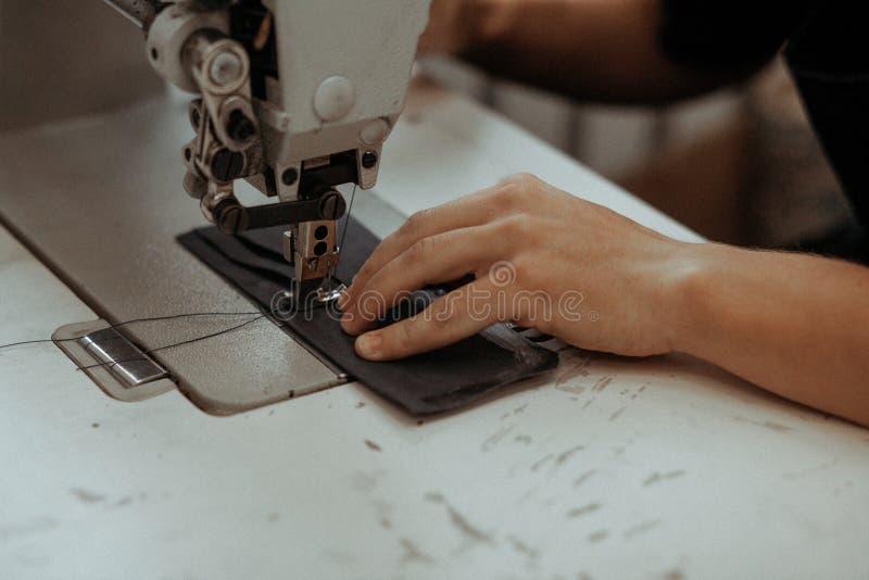 Fermez-vous de l'organe mobile de machine à coudre avec le cuir Les mains de maître coud un produit en cuir Concept fait main photos libres de droits