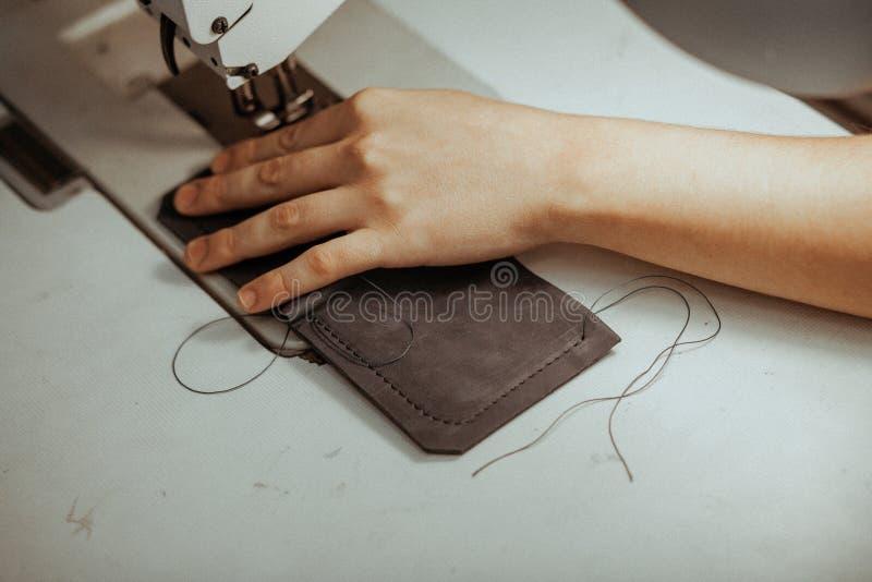 Fermez-vous de l'organe mobile de machine à coudre avec le cuir Les mains de maître coud un produit en cuir Concept fait main photographie stock libre de droits