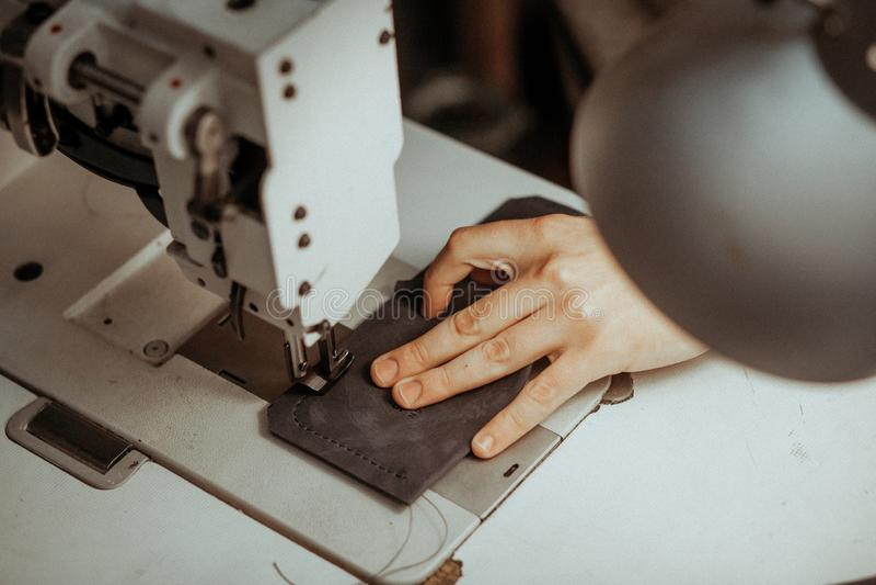 Fermez-vous de l'organe mobile de machine à coudre avec le cuir Les mains de maître coud un produit en cuir Concept fait main image stock