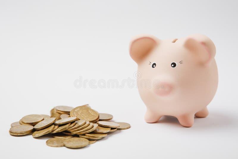 Fermez-vous de la banque porcine rose d'argent, pile des pièces de monnaie d'or sur le fond blanc de mur Accumulation d'argent image stock