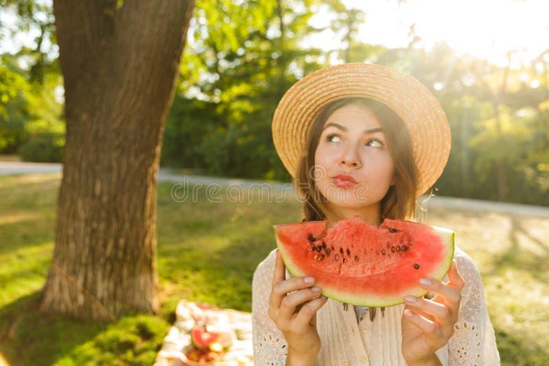 Fermez-vous de la belle jeune fille dans le temps de dépense de chapeau d'été au parc, images stock