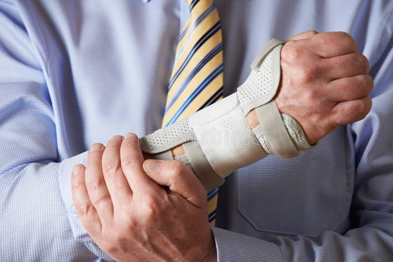 Fermez-vous de la blessure de tension de Suffering With Repetitive d'homme d'affaires image stock