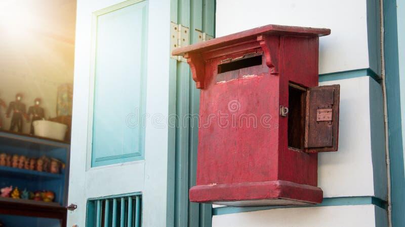 Fermez-vous de la boîte aux lettres en bois de vieux cru rouge devant le magasin de cru images libres de droits