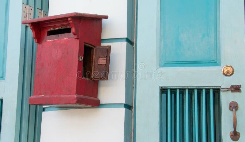 Fermez-vous de la boîte aux lettres en bois de vieux cru rouge devant le magasin de cru image libre de droits
