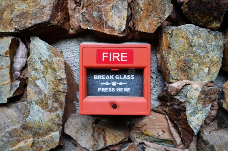 Fermez-vous de la boîte d'alarme d'incendie sur le mur en pierre Machine rouge de presse d'alarme d'incendie photographie stock