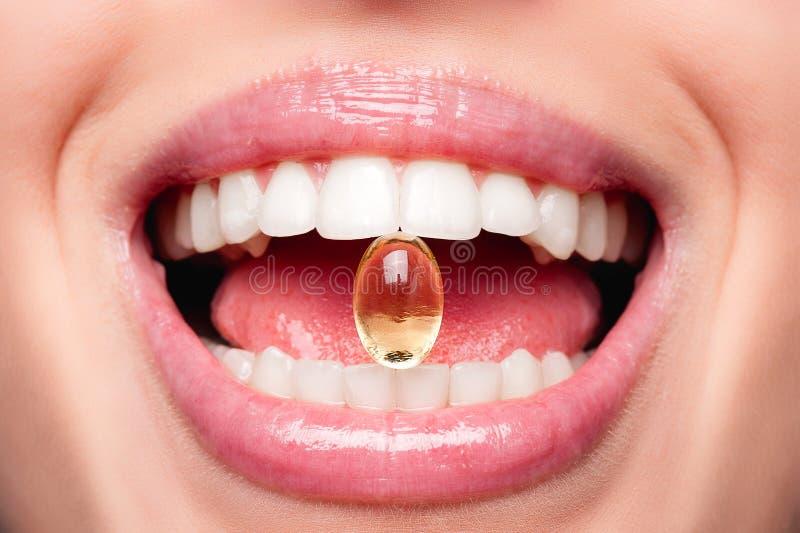 Fermez-vous de la bouche ouverte belle par femme tenant la pilule d'huile de poisson dans des dents blanches Capsule de sourire d image libre de droits