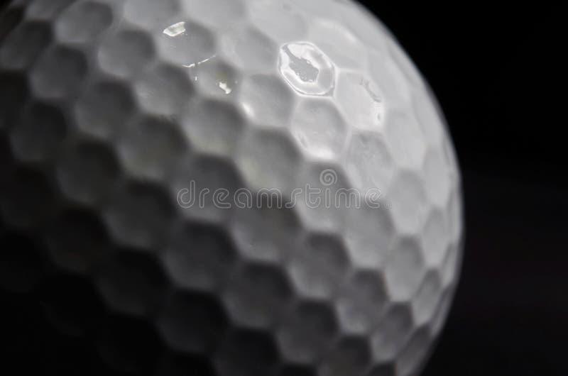 Fermez-vous de la boule de golf sur le fond noir image stock