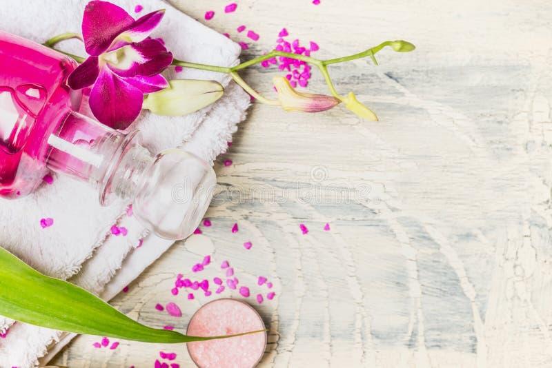 Fermez-vous de la bouteille en verre de lotion avec les fleurs roses d'orchidée sur la serviette blanche sur le fond en bois clai photographie stock libre de droits