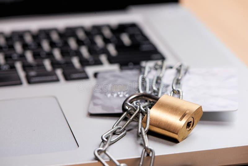 Fermez-vous de la carte de crédit et de l'ordinateur portable avec la chaîne et le cadenas photographie stock libre de droits