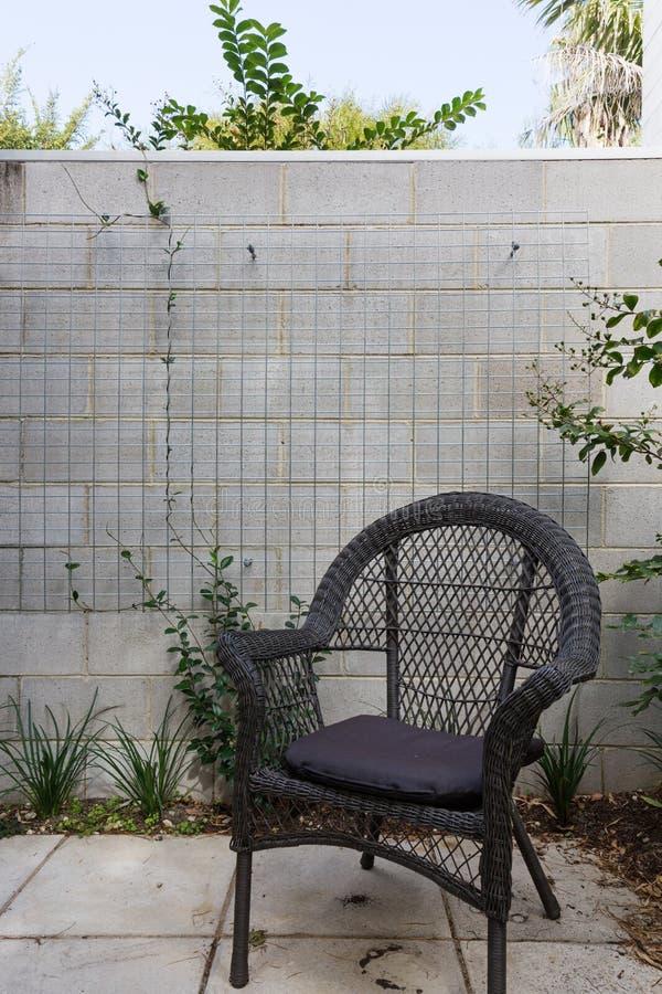 Fermez-vous de la chaise extérieure de canne noire dans la cour contre le bloc photos stock