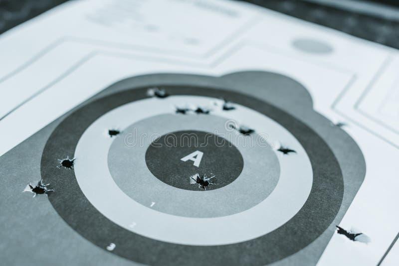 fermez-vous de la cible utilisée d'arme à feu avec des trous après des balles images stock