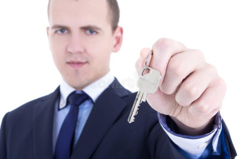 Fermez-vous de la clé en métal dans la vraie main masculine d'agent immobilier d'isolement dessus photographie stock