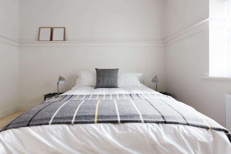 Fermez-vous de la couverture de jet de laine grise sur le lit de luxe d'invité photos stock