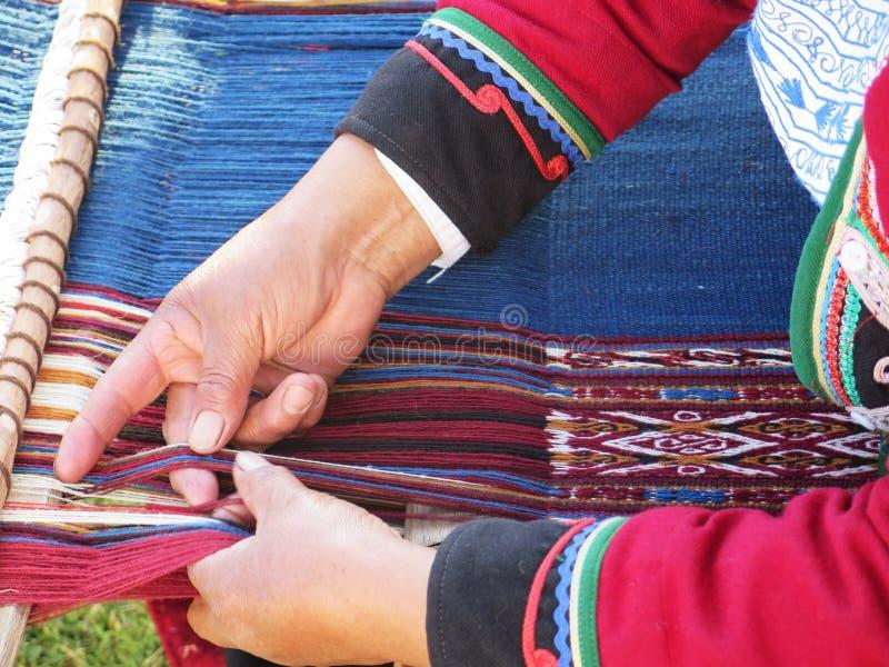Fermez-vous de la dame péruvienne en fil de rotation authentique de robe par l'ha photographie stock libre de droits