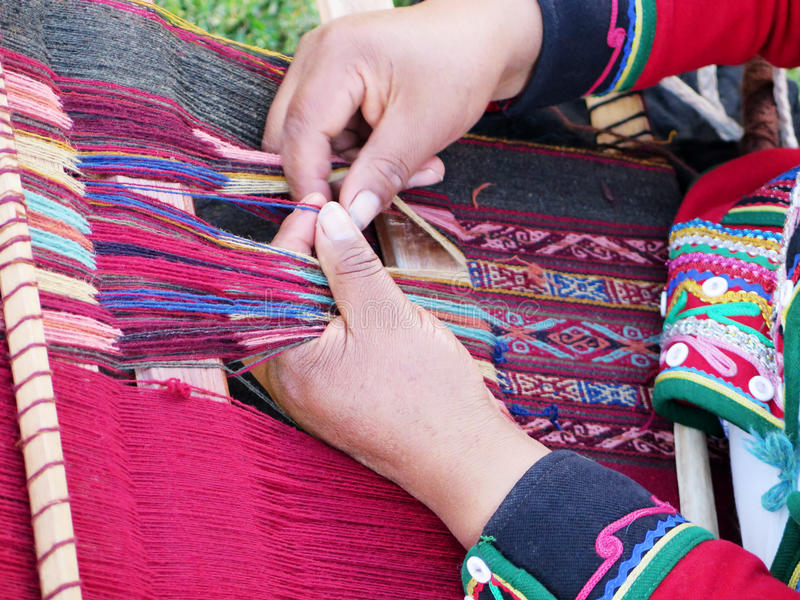 Fermez-vous de la dame péruvienne en fil de rotation authentique de robe par l'ha images stock
