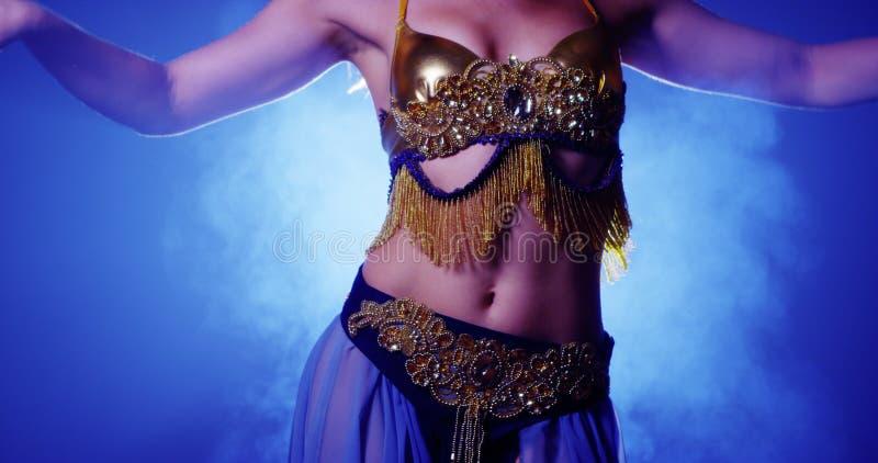 Fermez-vous de la danseuse du ventre en bleu et or photo stock