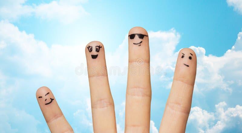 Fermez-vous de la famille de quatre doigts avec les visages souriants photo stock