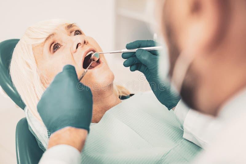 Fermez-vous de la femme agée dans la chaise dentaire photo libre de droits