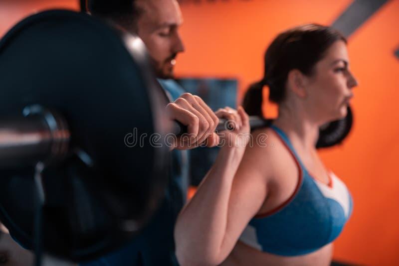 Fermez-vous de la femme de aide d'entraîneur bel avec le barbell de levage photo stock