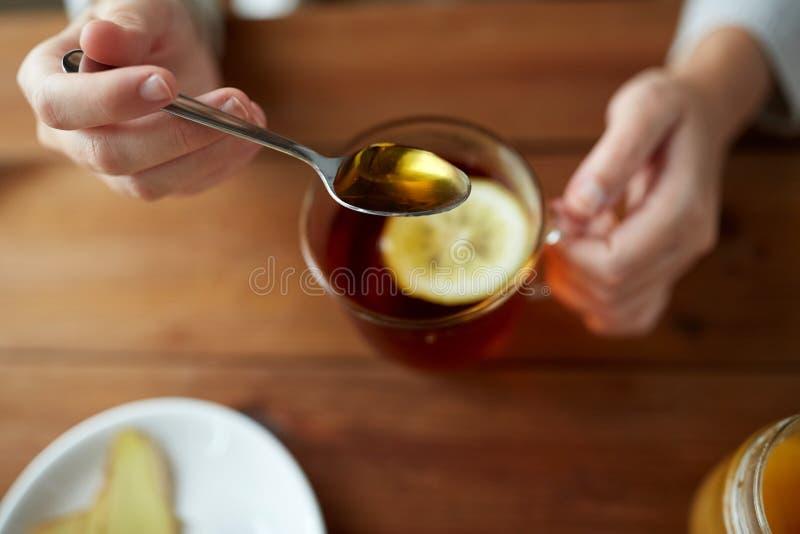 Fermez-vous de la femme ajoutant le miel au thé avec le citron images libres de droits