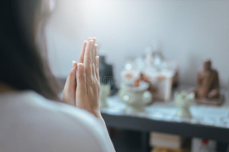 Fermez-vous de la femme asiatique avec la main dans des postures de prière de culte, les mains femelles de prière a étreint ensem image libre de droits