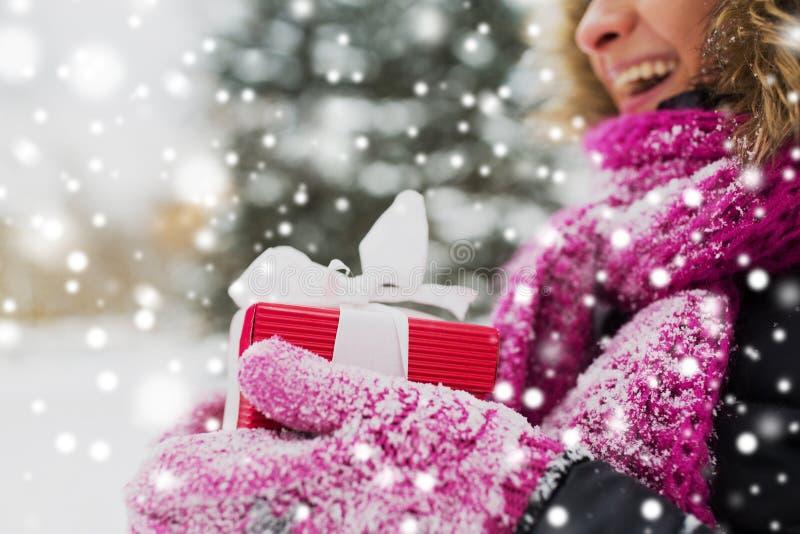 Fermez-vous de la femme avec le cadeau de Noël dehors photos libres de droits