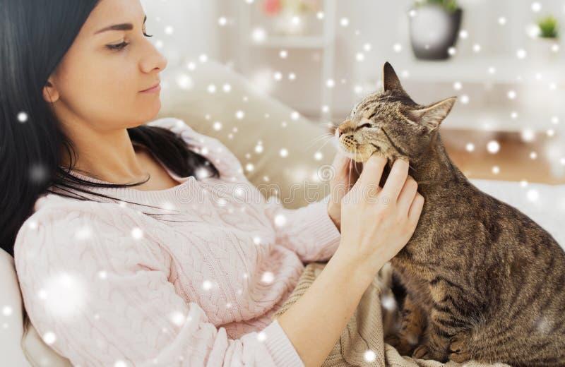Fermez-vous de la femme avec le chat tigré dans le lit à la maison photographie stock libre de droits