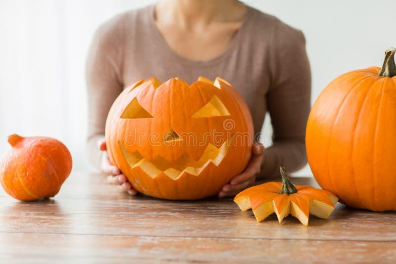 Fermez-vous de la femme avec le potiron de Halloween à la maison images libres de droits